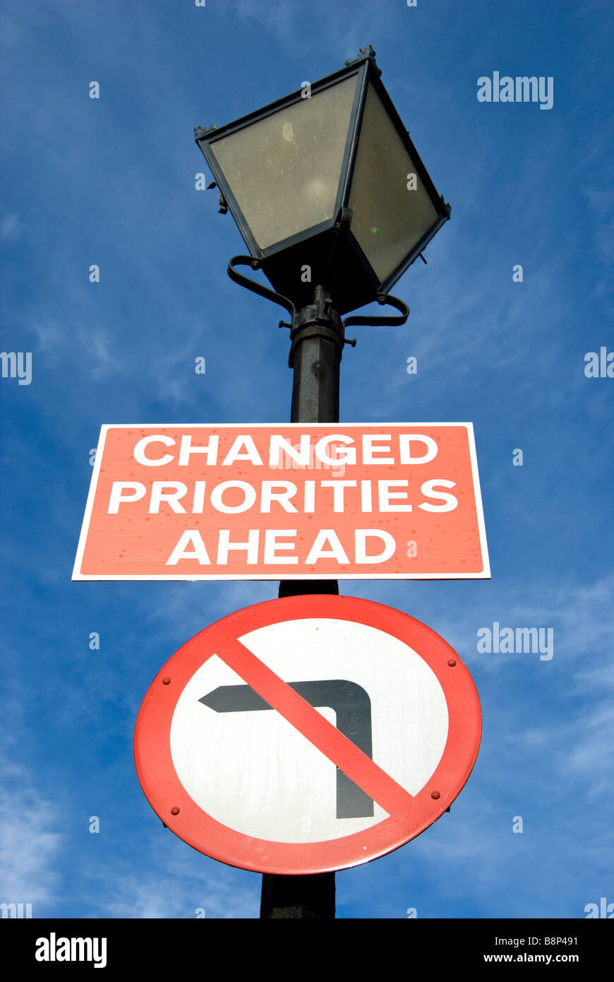 british road signs fixed to a lampost stating changed priorities ahead and no left turn - Stock Image