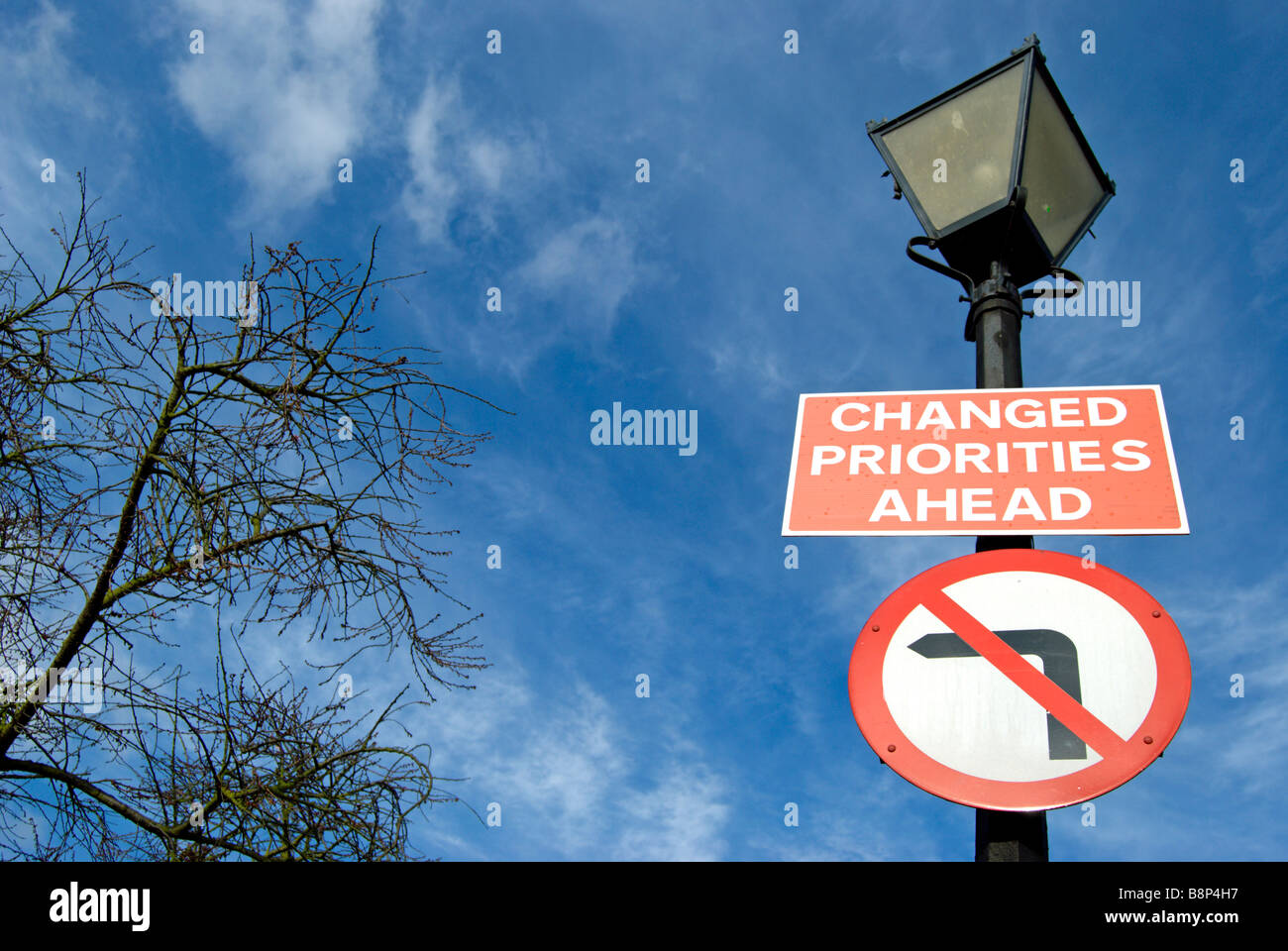 british road signs fixed to a lamppost stating changed priorities ahead and no left turn - Stock Image