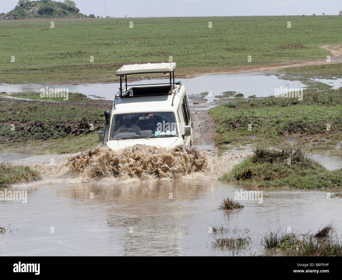 Africa Tanzania Serengeti National Park Safari tourists in an open top land rover crossing a water barrier - Stock Image