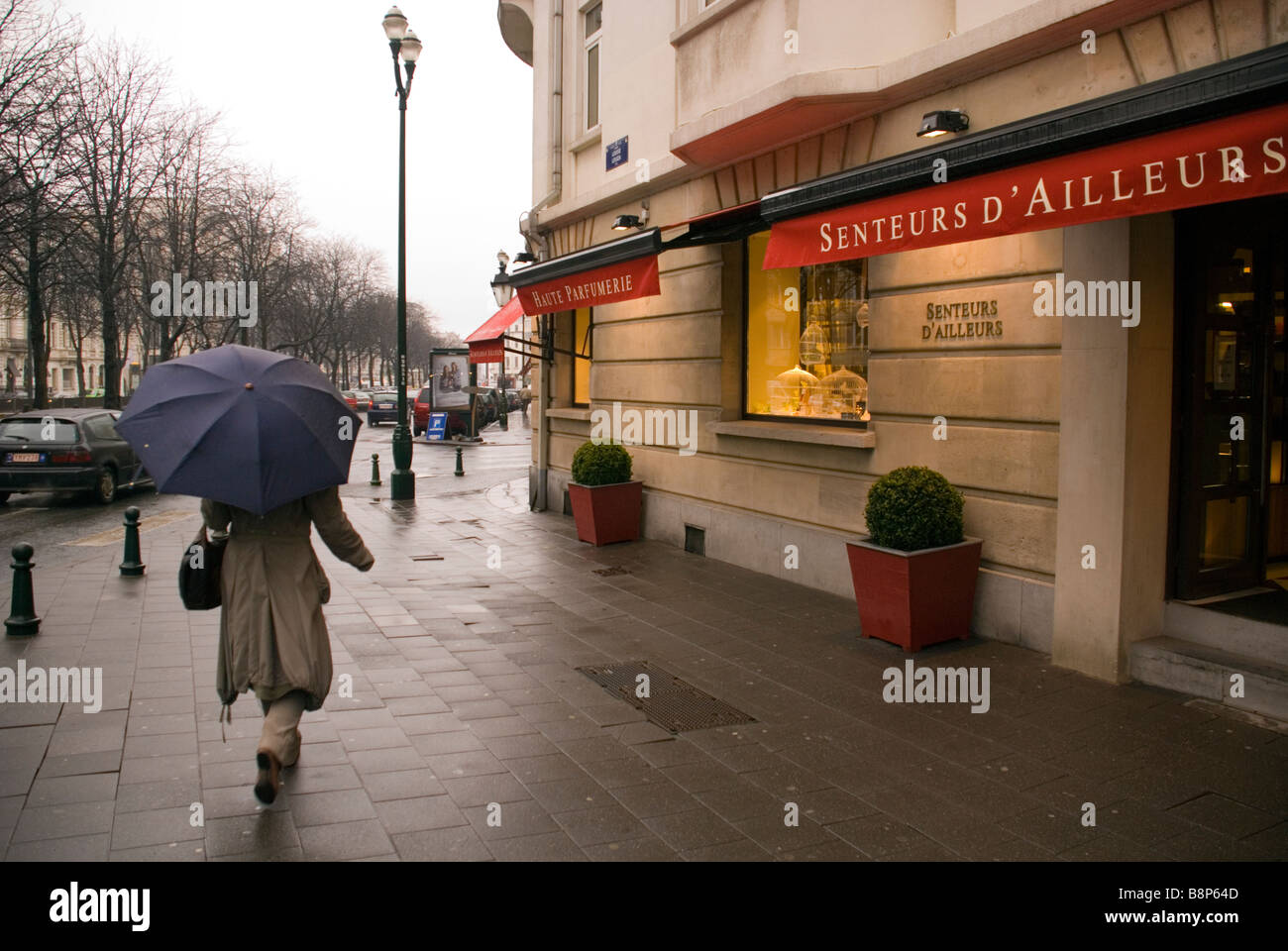 Brussels Belgium Avenue Louise A woman walks past a perfume shop in the rain - Stock Image