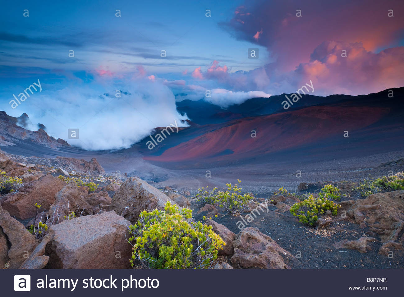 Storm clouds climb up the crater in Haleakala National Park on the Hawaiian island of Maui at sunset. - Stock Image