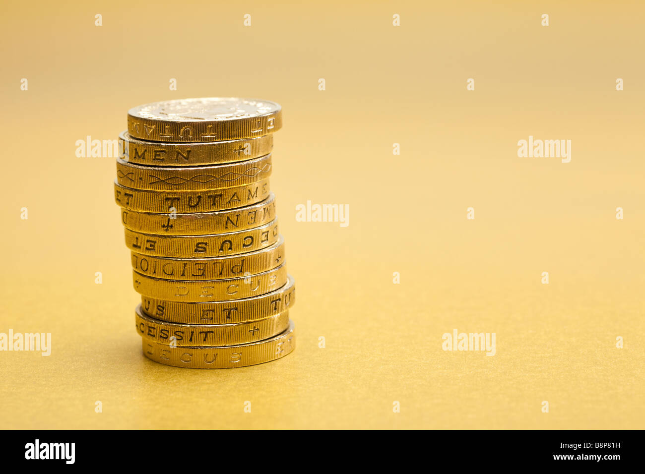 Stack of £1 one pound coins sterling on gold background - Stock Image