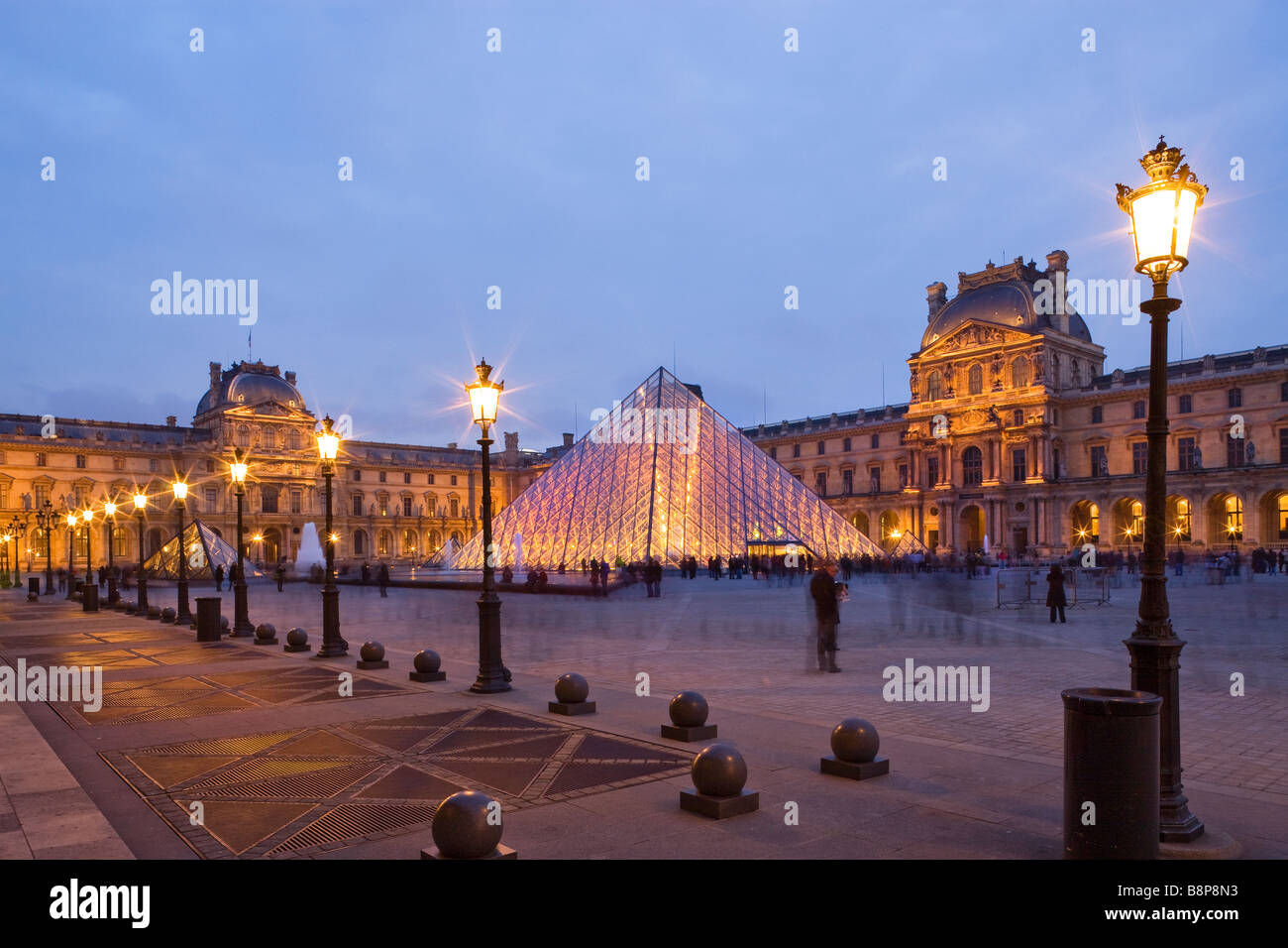 The Louvre Museum illuminated glass pyramid entrance Paris France - Stock Image