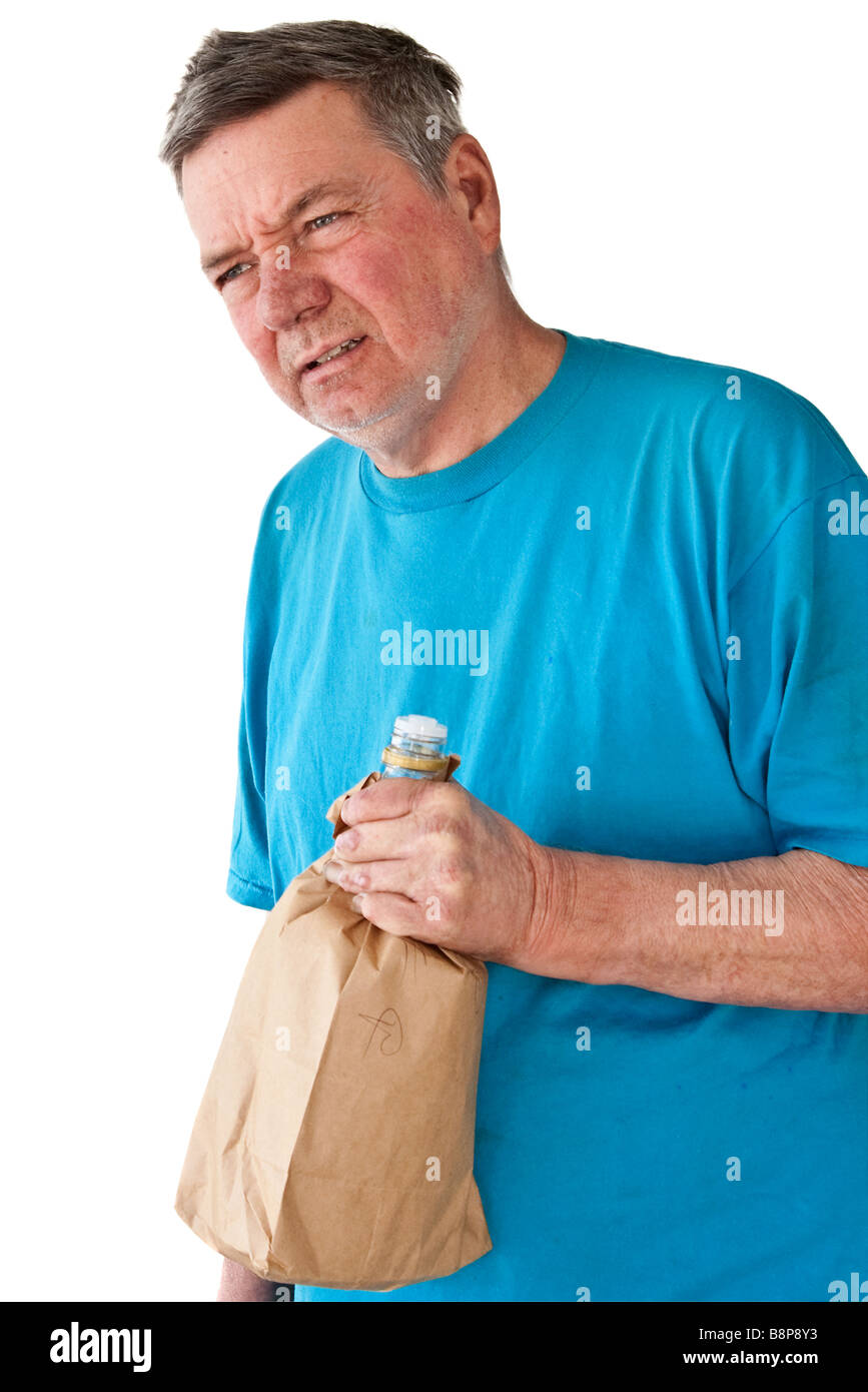 Distraught mature man with bottle of booze in paper bag isolated on white background - Stock Image