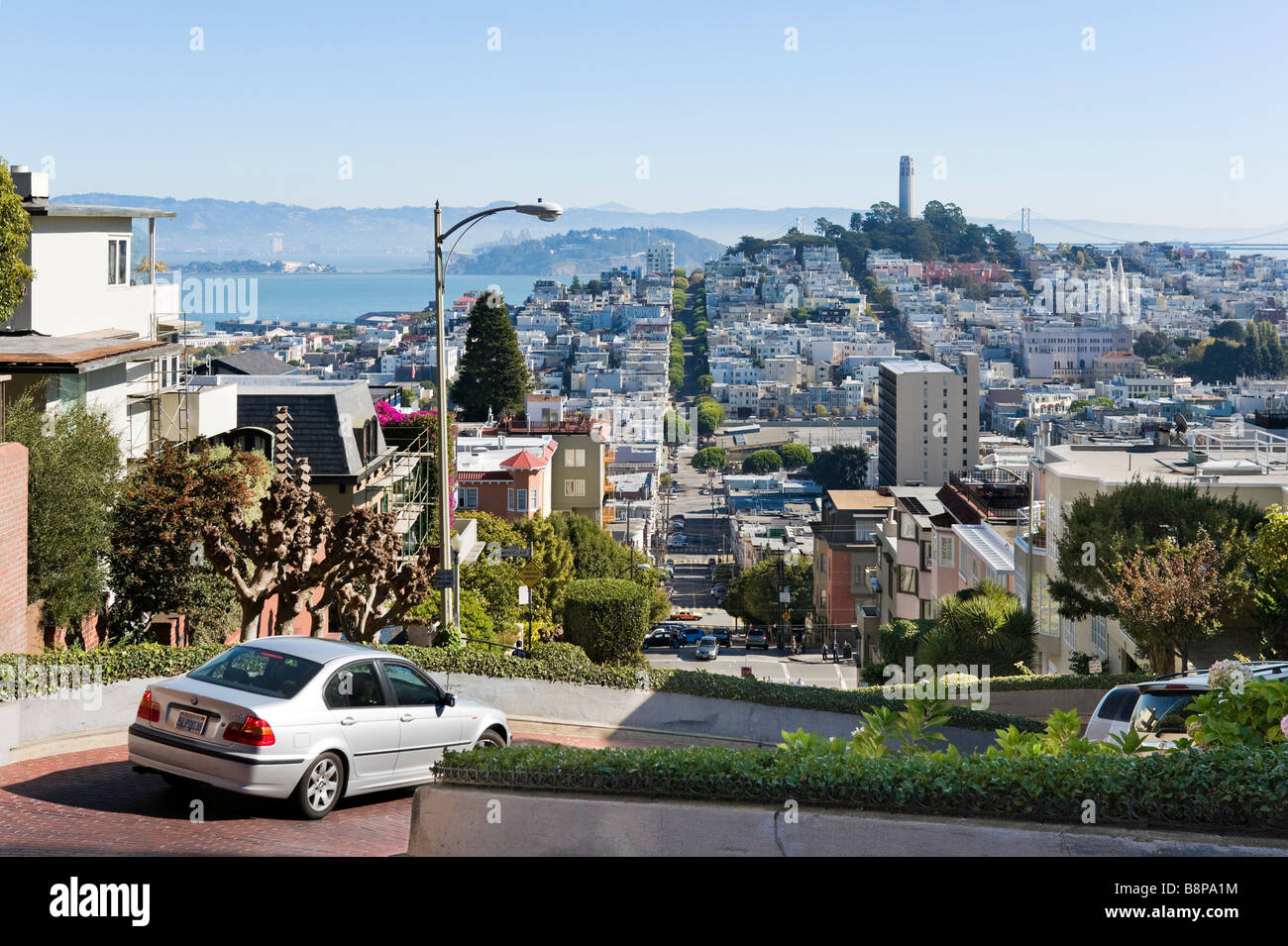 View down Lombard Street towards the Coit Tower, Telegraph Hill and North Beach, San Francisco, California, USA - Stock Image