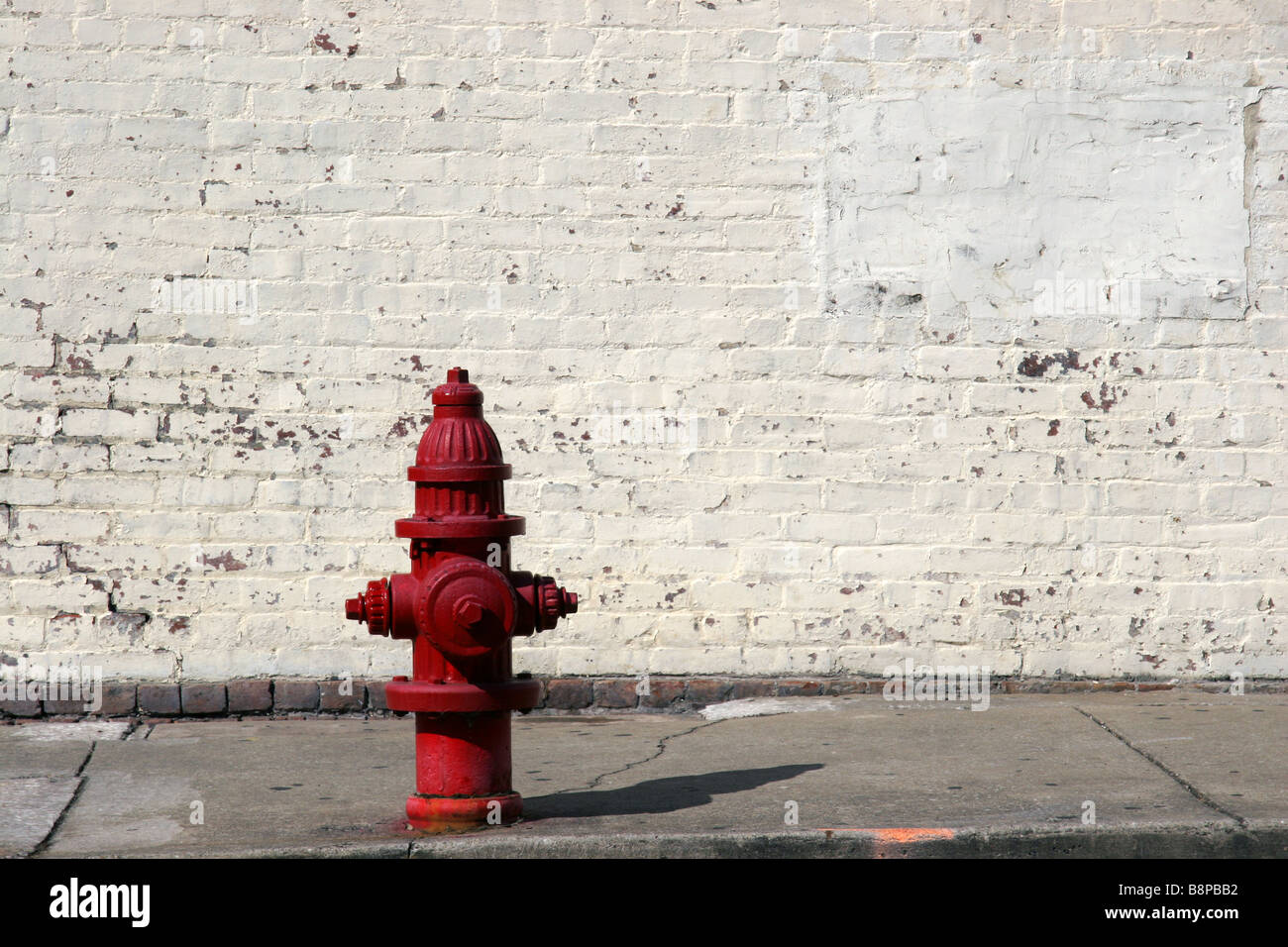Red American fire hydrant and white brick wall - Stock Image