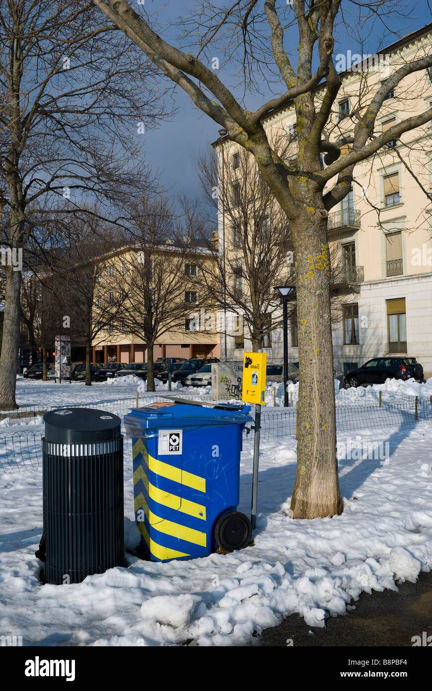 A recycling bin sits next to a city trash can surrounded by snow; Neuchatel Switzerland - Stock Image