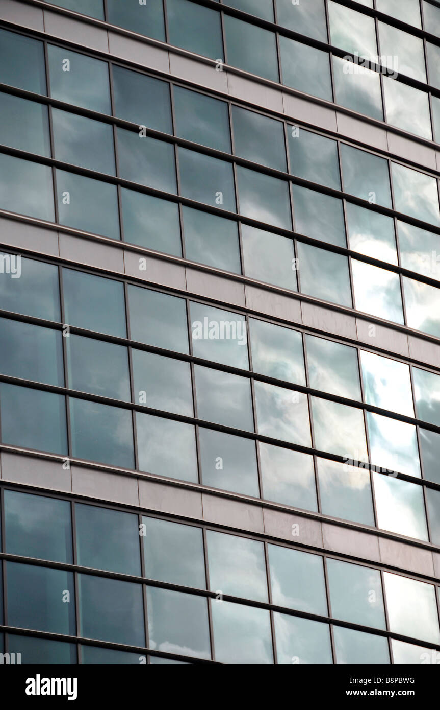 modern glass frontage of new office block tinted relective clouds panes architecture - Stock Image