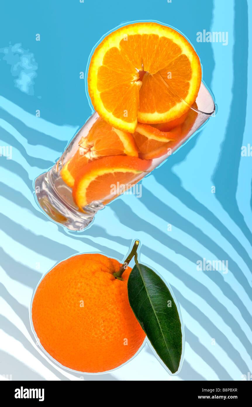 Orange, glass with oranges and slice of orange fruit,orange juice on blue background - Stock Image