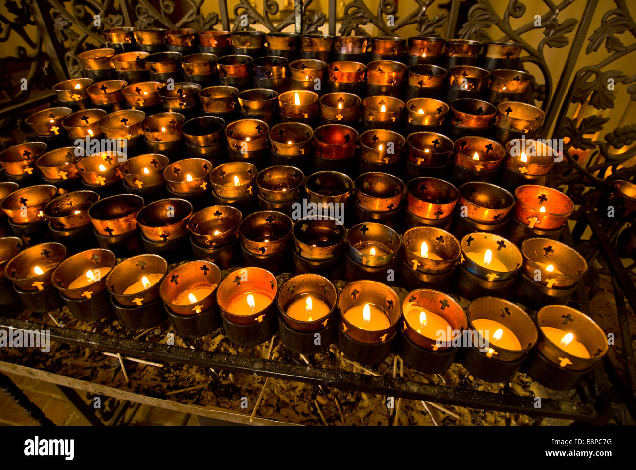 votive candles inside church rack of dozens of candles burning religious ceremony custom practice - Stock Image