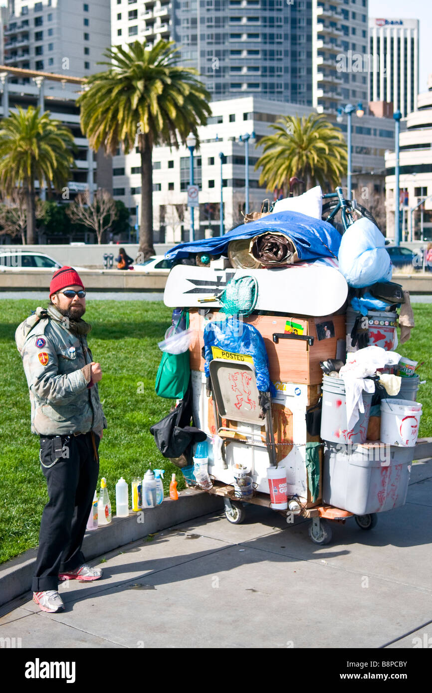 Homeless man standing with possessions on cart in Rincon Park in San Francisco California asking for money 'Editorial - Stock Image