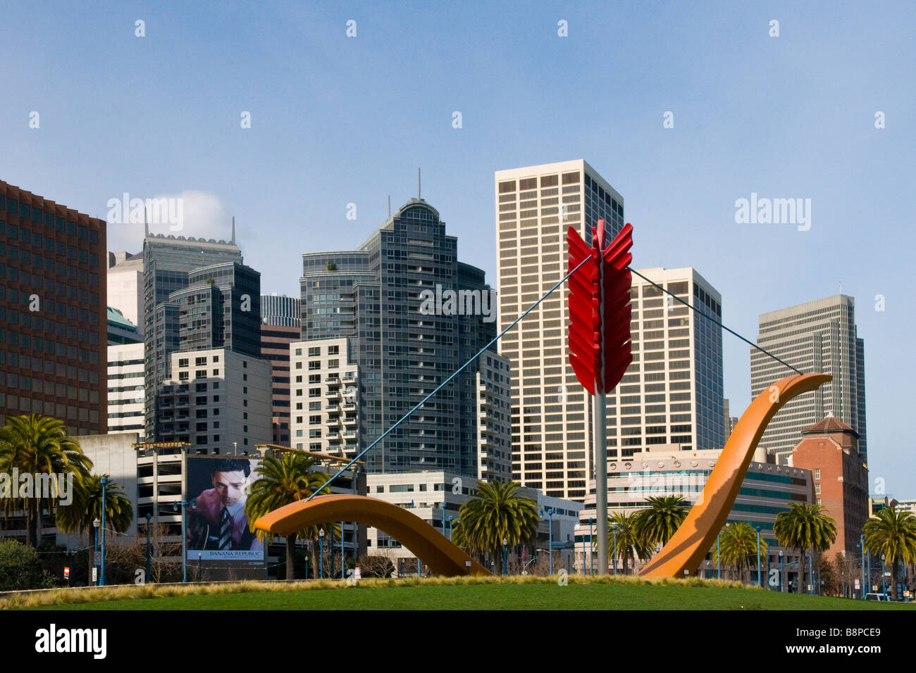 Large sculpture of bow and arrow in Rincon Park with San Francisco skyline in background - Stock Image