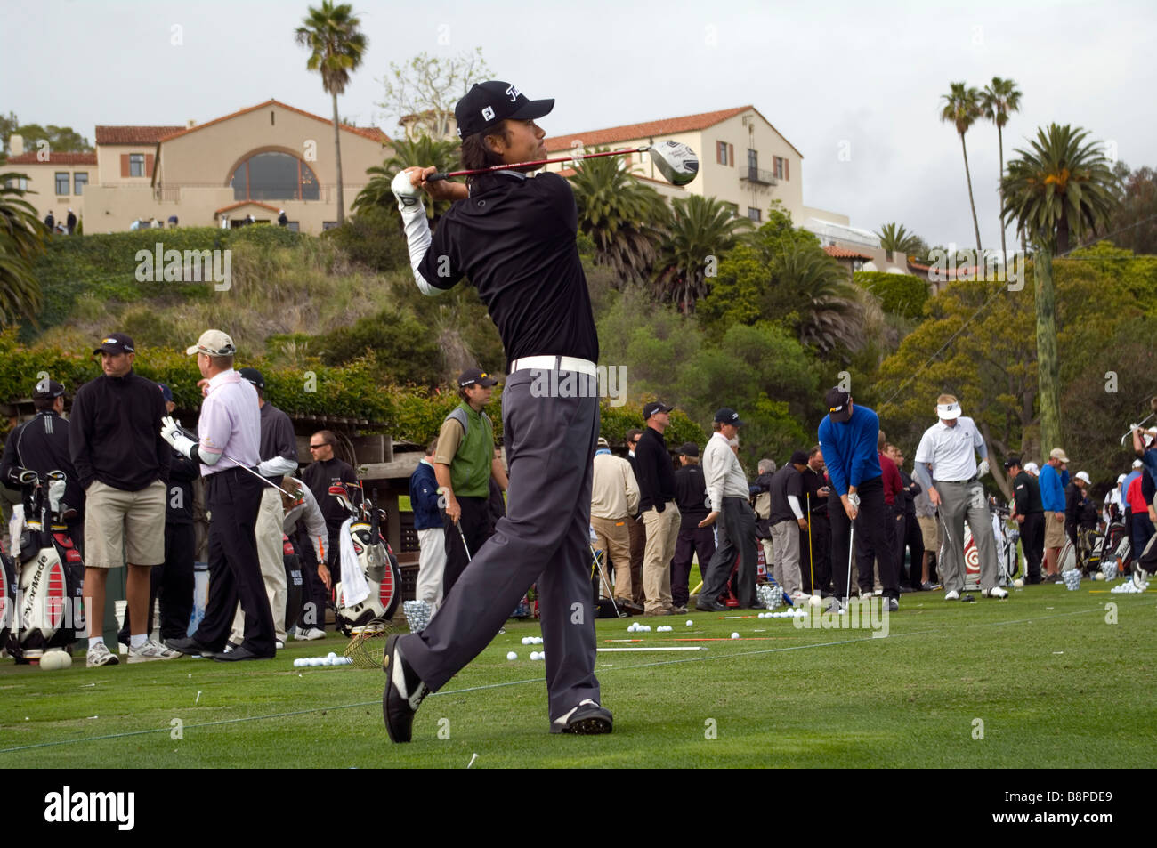 Kevin Na hits some balls at the driving range at the Northern Trust Open. - Stock Image
