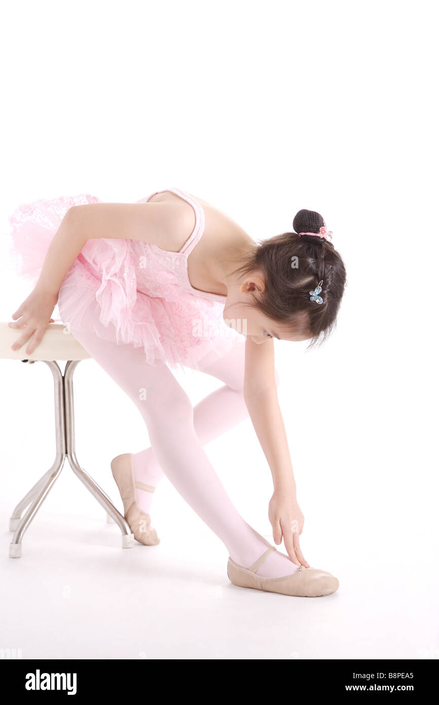 Ballet dancer sitting on stool touching her foot portrait - Stock Image