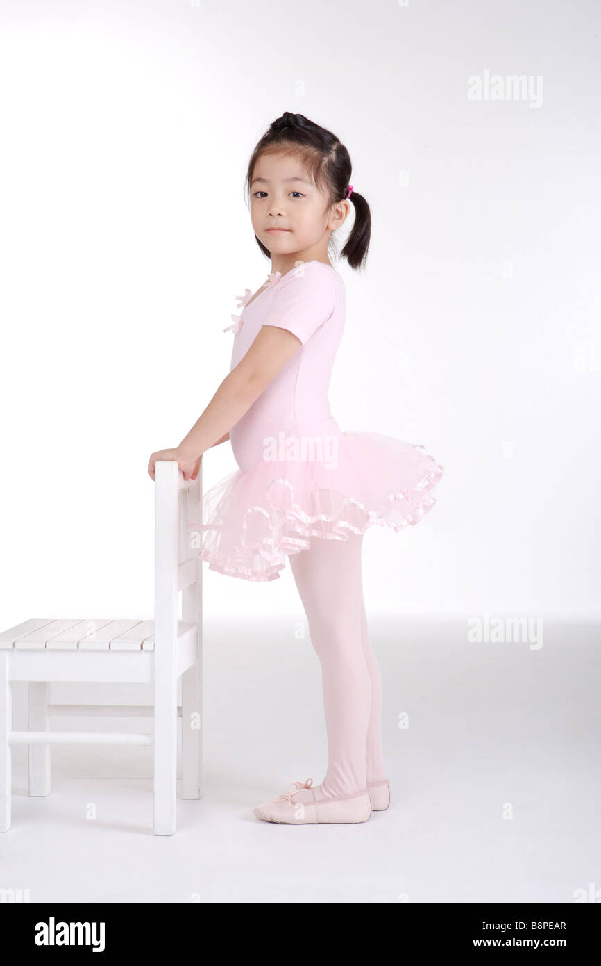 Girl ballet dancing with chair side view portrait - Stock Image