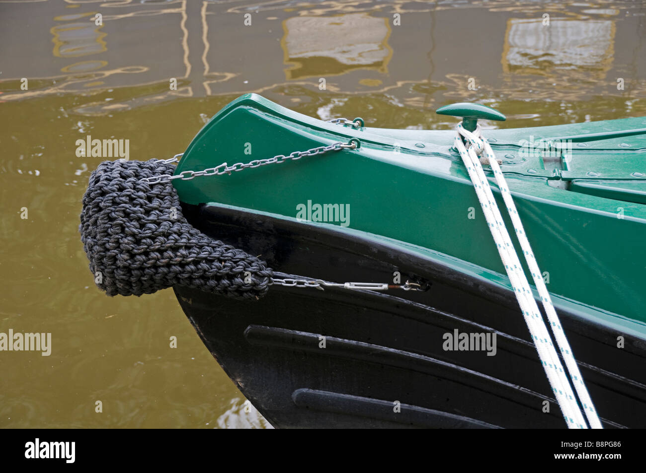 The bow of a longboat secured to side of canal with line - Stock Image