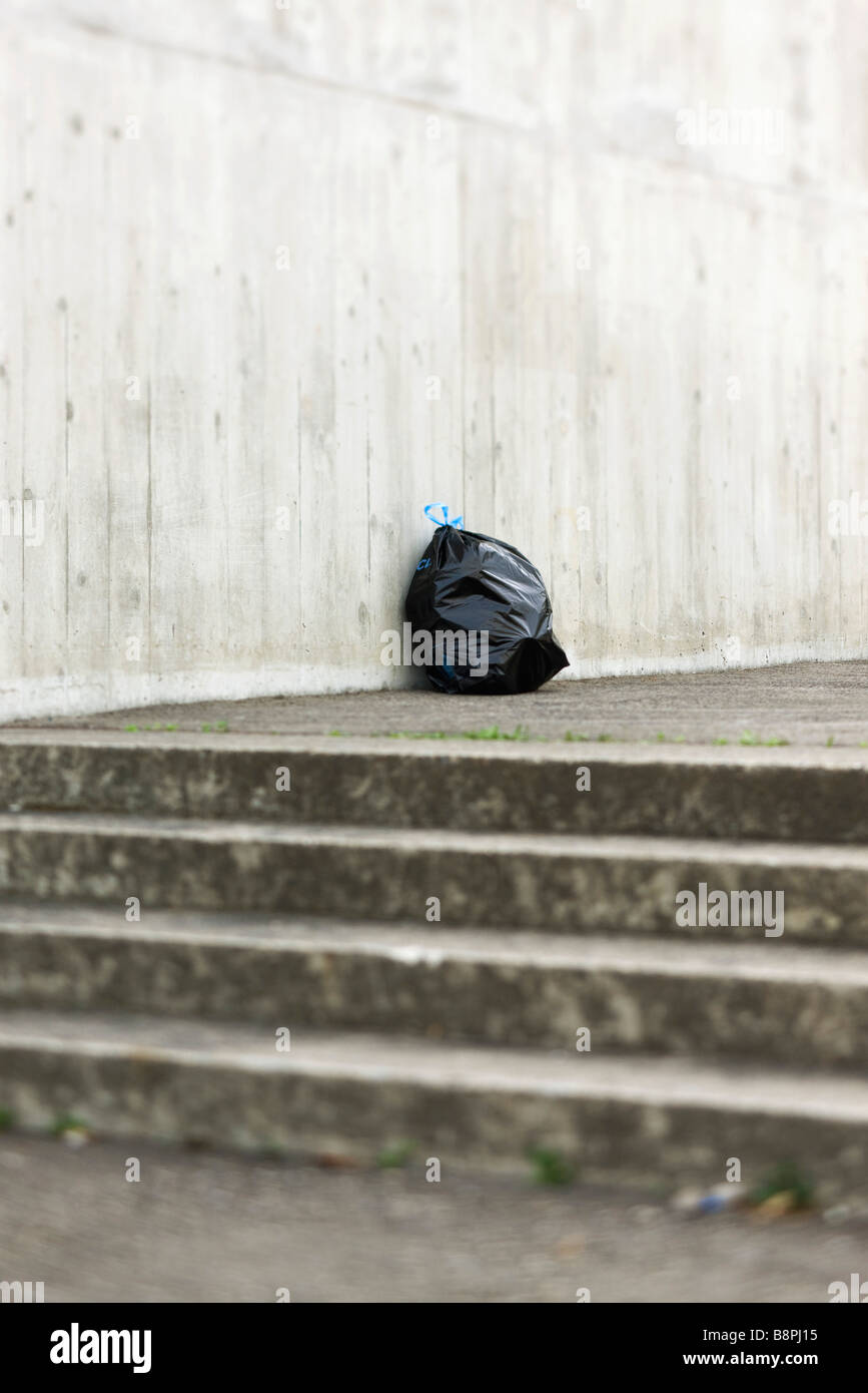 Bag of garbage sitting at top of steps - Stock Image