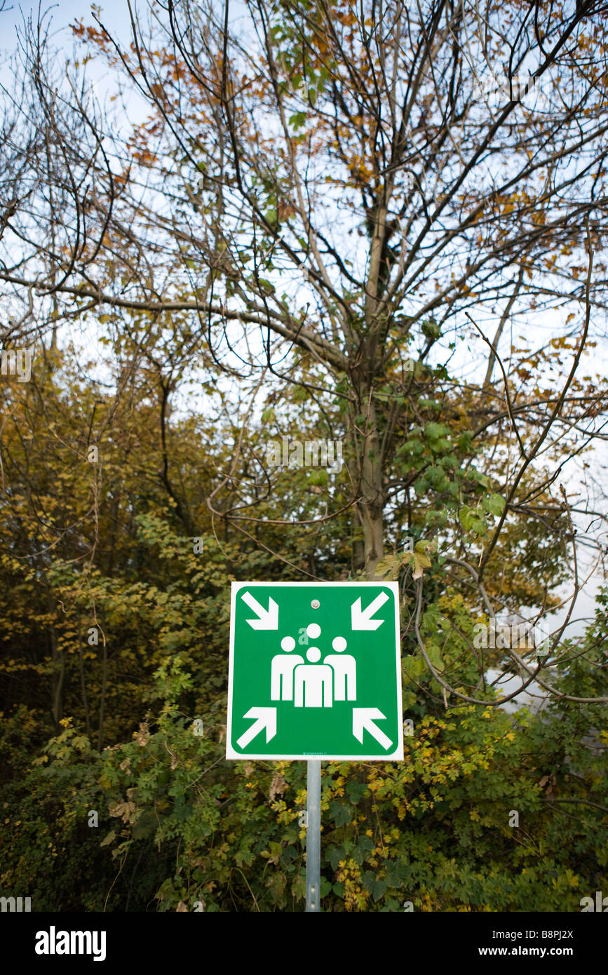 Emergency assembly sign in wooded area - Stock Image