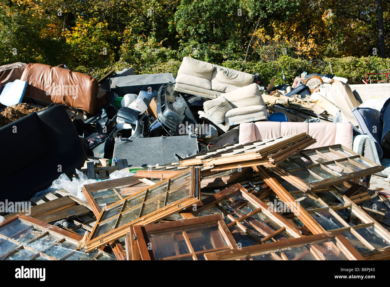 Discarded windows and furniture in large junk heap Stock Photo