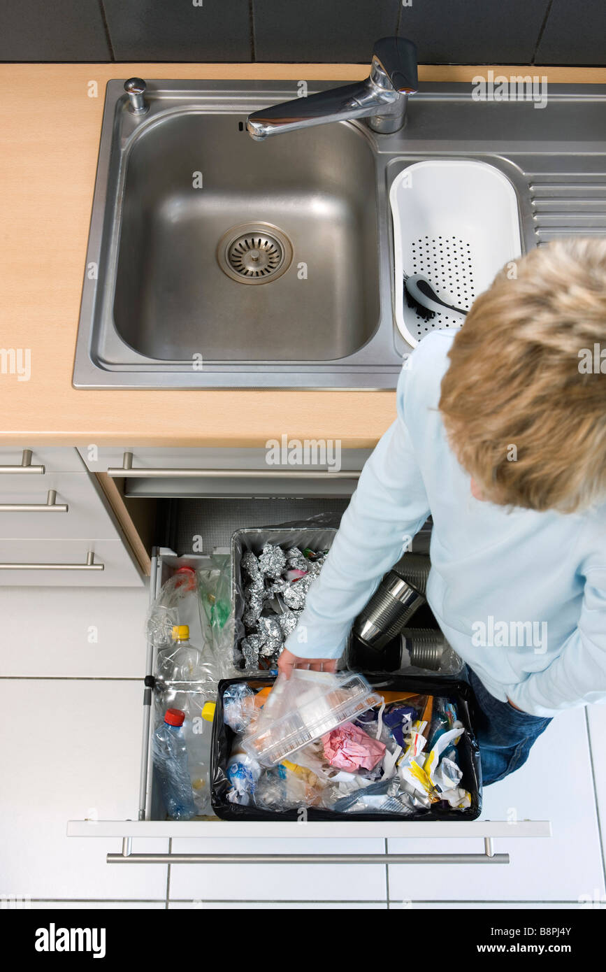 Child placing plastic container in trash can rather than nearby recycling bins Stock Photo