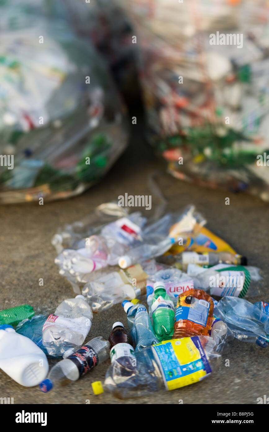 Crushed plastic bottles on ground, garbage bags in background - Stock Image