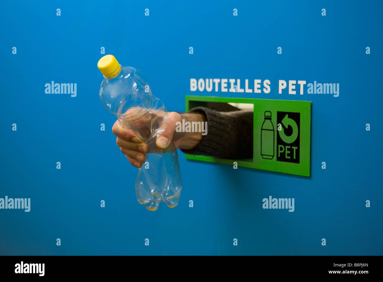 Hand reaching from inside recycling receptacle, holding plastic bottle - Stock Image