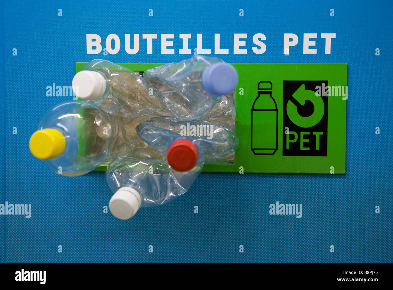 Plastic bottles spilling out of recycling bin - Stock Image