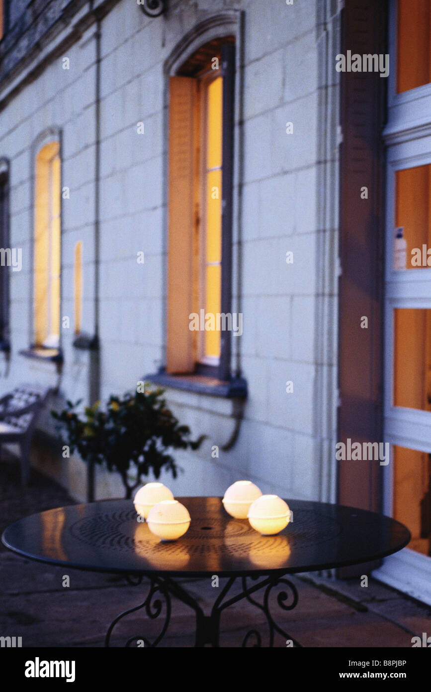 Decorative candle holders on table outside house - Stock Image