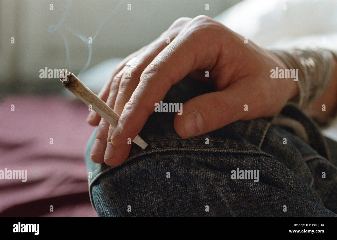 Hand holding smoking joint Stock Photo