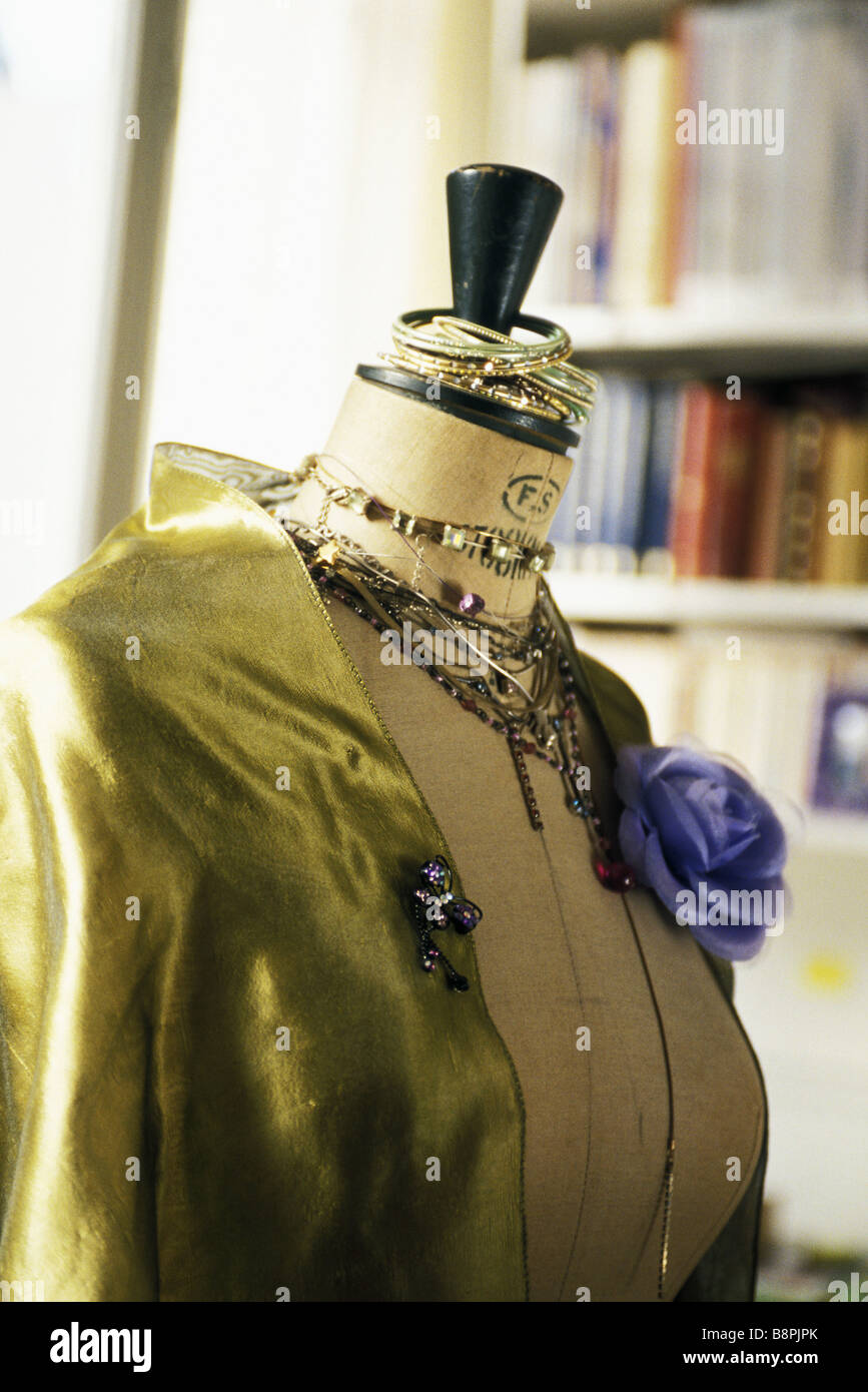 Mannequin displaying satin blouse, jewelry - Stock Image