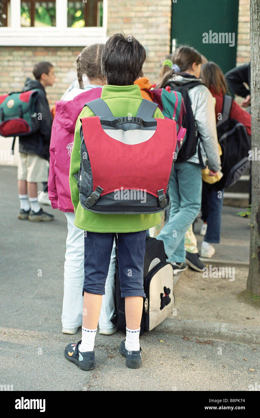 Children filing into elementary school entrance - Stock Image