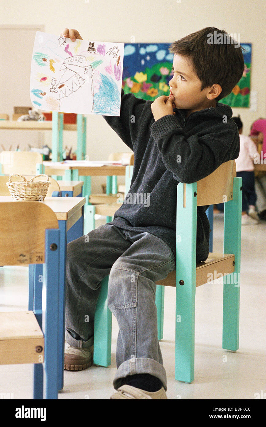 Boy holding up drawing in class room Stock Photo