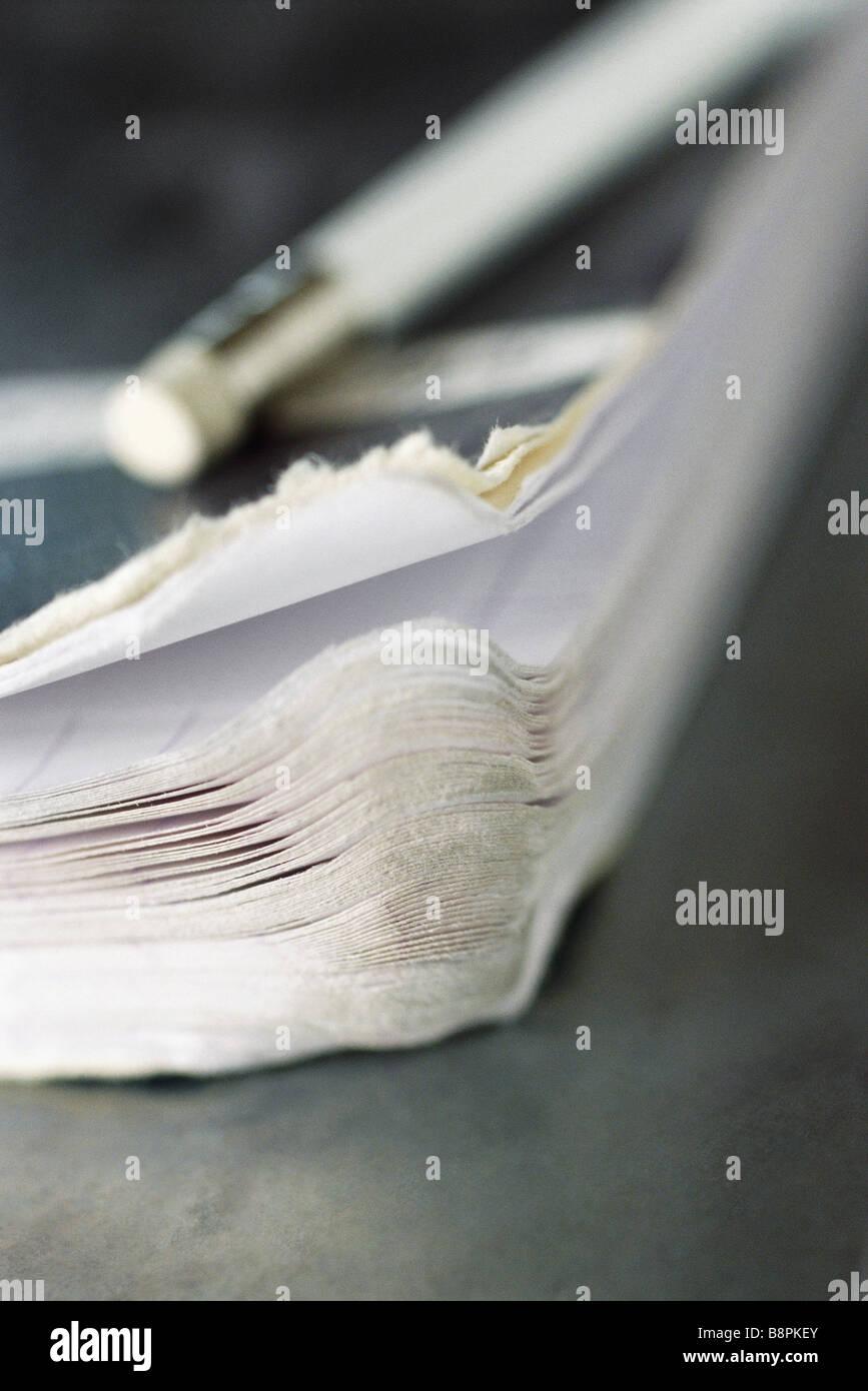 Corner of notebook ad pencil - Stock Image