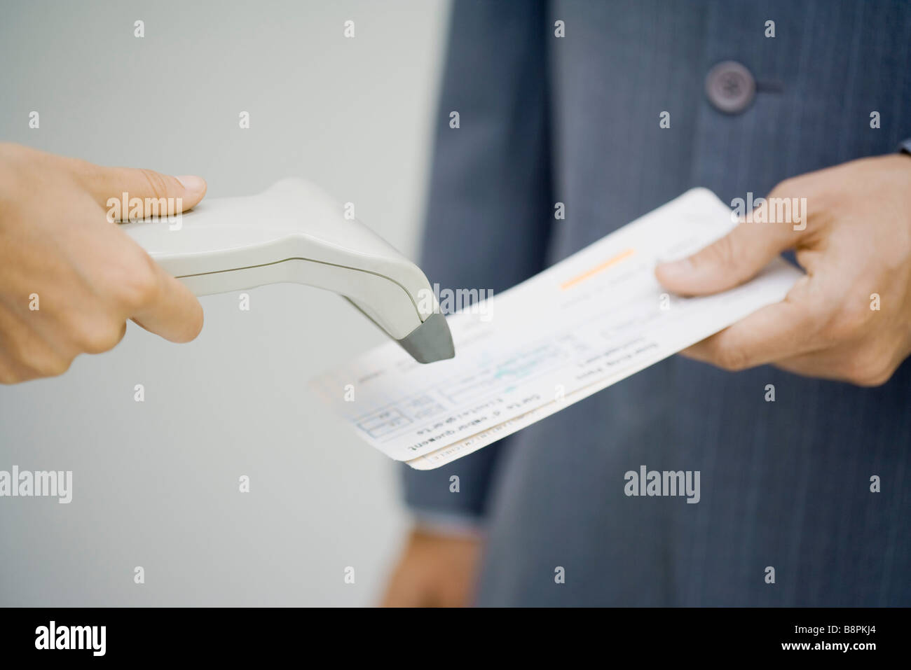 Man's plane tickets being scanned - Stock Image