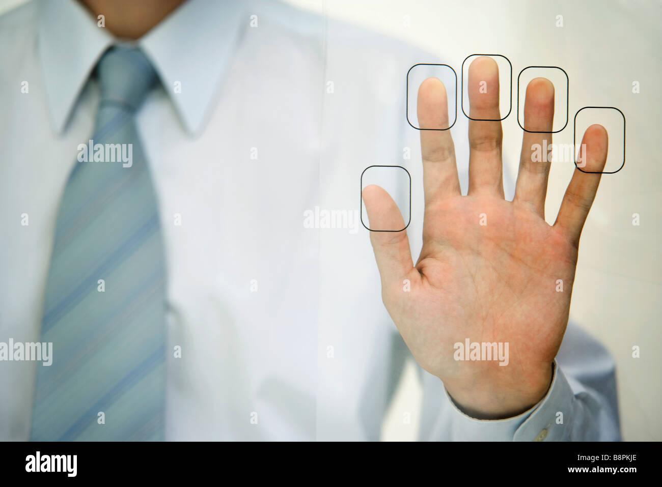Man pressing fingertips to fingerprint reader - Stock Image