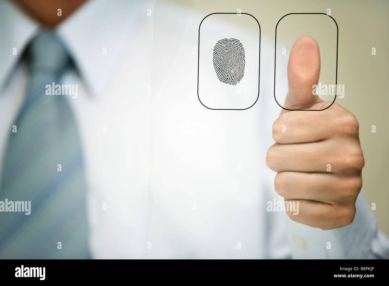 Man pressing thumb to fingerprint reader - Stock Image