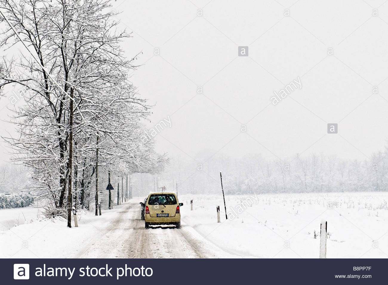 motor vehicle on the road covered with snow - Stock Image