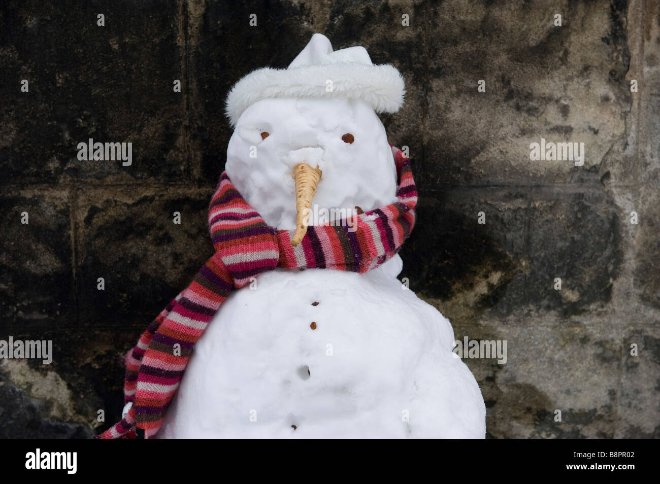 A snowman with college scarf in Oxford - Stock Image