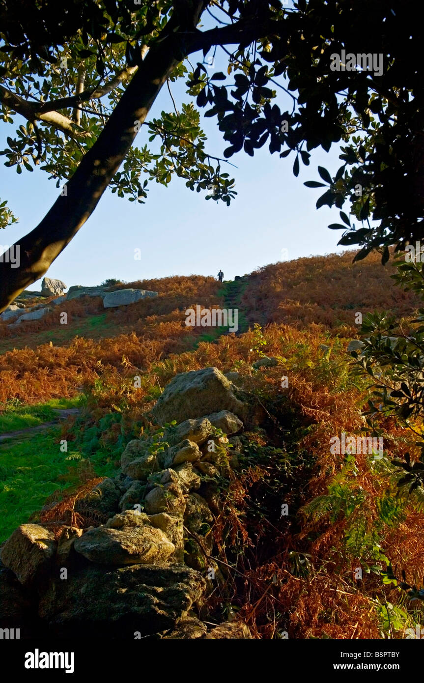 A  silhouetted rambler at the top of a hill along the coastal footpath. St Mary's. The Isles of Scilly. Cornwall. - Stock Image