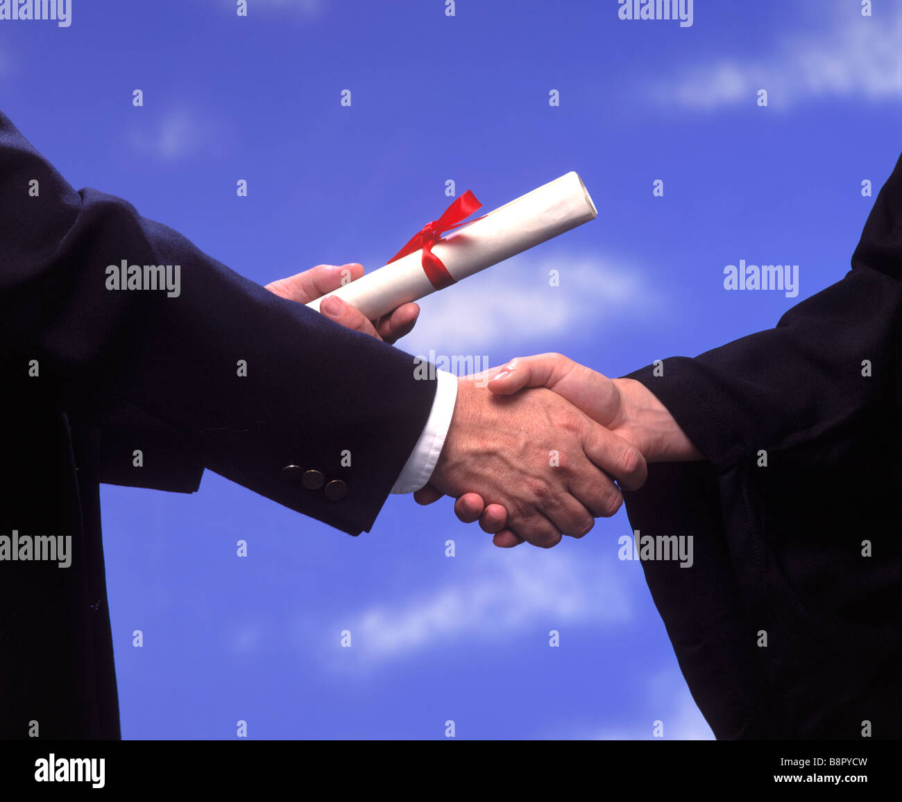 A diploma is presented to a college graduate with a handshake - Stock Image