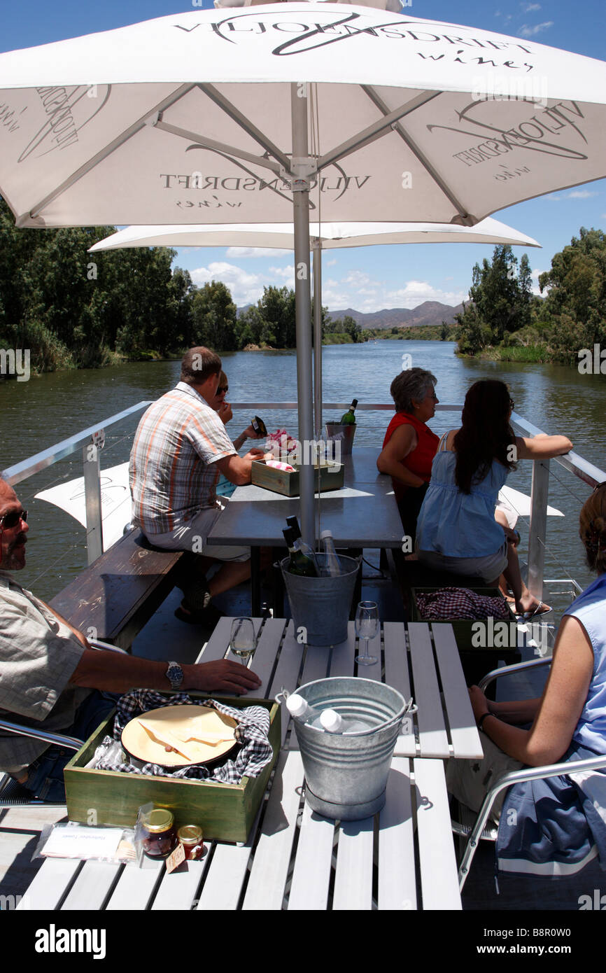 people enjoying a river cruise while drinking wine from the viljoensdrift winery robertson wine valley western cape - Stock Image