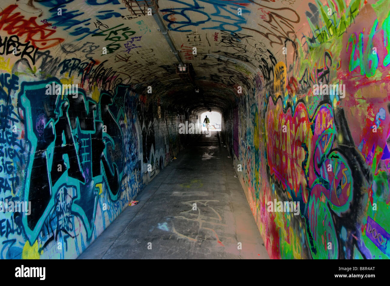 A man exits a graffitied tunnel. - Stock Image