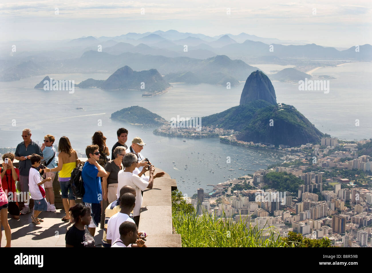 TOURISTS VIEW RIO DE JANEIRO FROM CORCOVADO HILL, BELOW CHRIST THE REDEEMER STATUE LOOKING TOWARDS SUGARLOAF MOUNTAIN Stock Photo