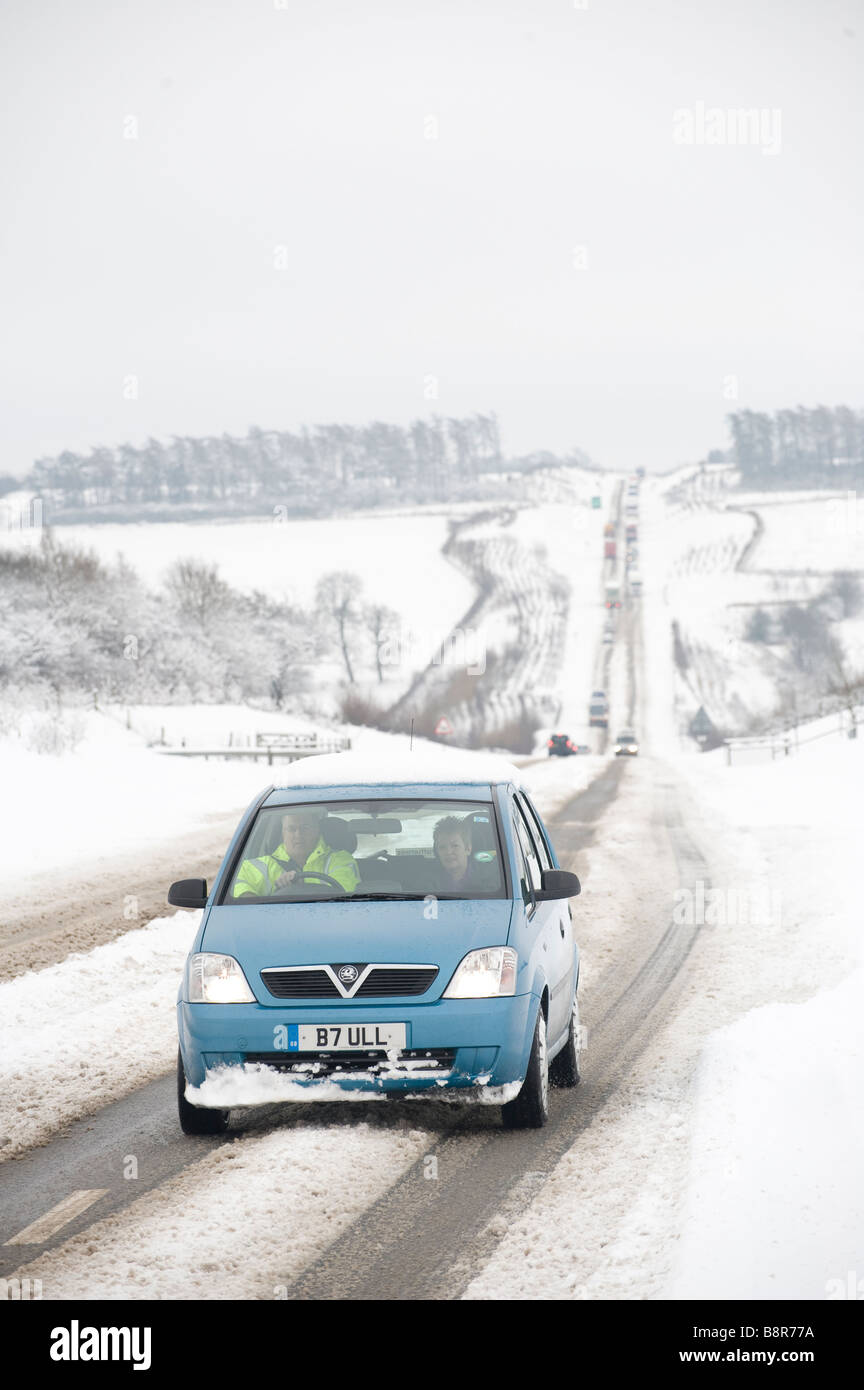 Small vauxhall car being driven on snow covered roads in the English countryside - Stock Image