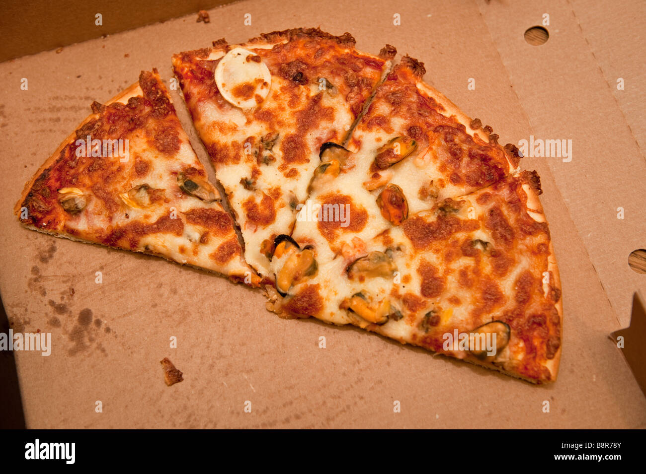 A Half eaten convenience fast food takeaway pizza in a box UK - Stock Image