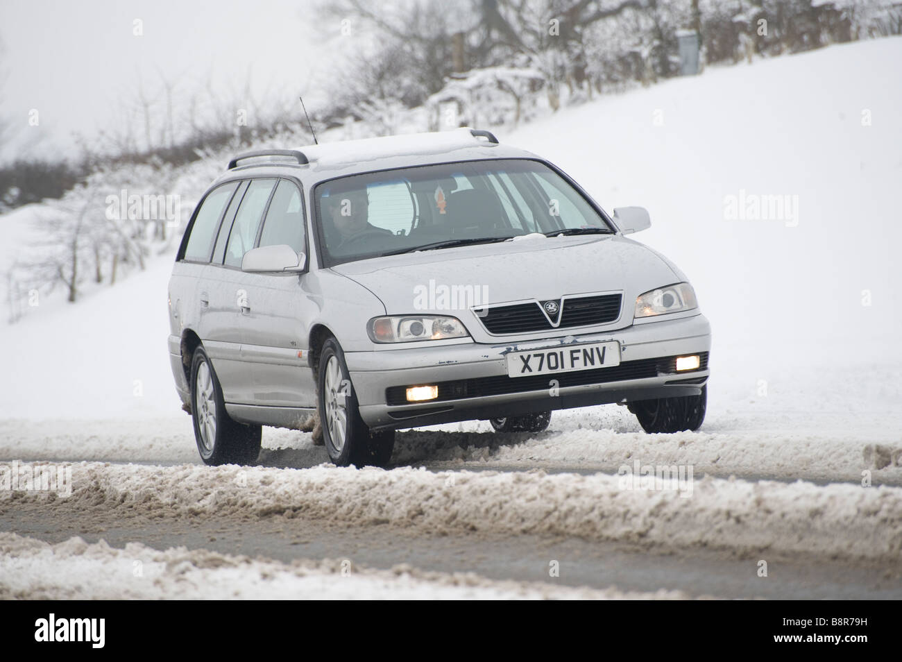 Silver vauxhall car being driven on snow covered roads in the English countryside - Stock Image