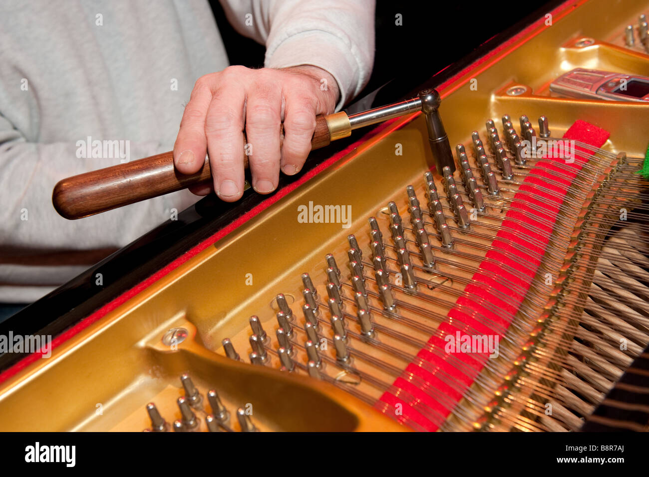 Detail of the hands of a man piano tuner tuning a grand piano before a concert, UK - Stock Image