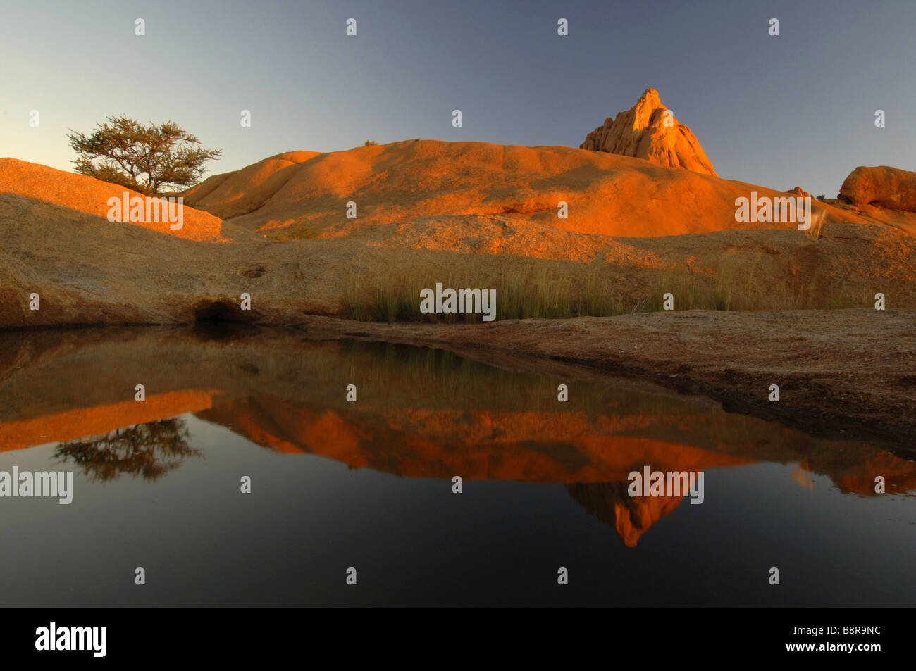 Spitzkoppe mirroring on water surface in evening light, Namibia Stock Photo