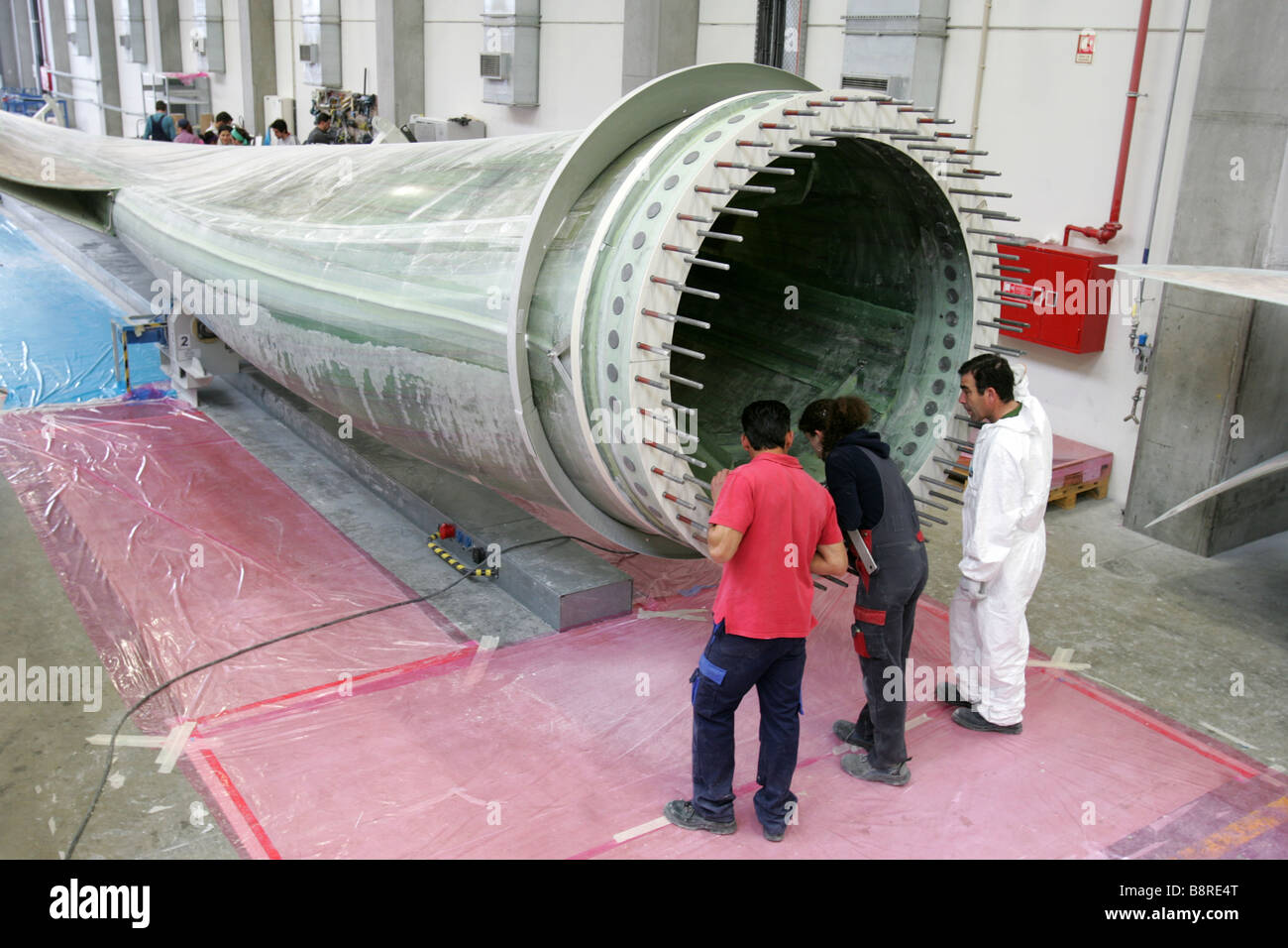 Workers next to a giant wind turbine blade at the factory VentoMoinho at Viana do Castelo, Portugal. - Stock Image