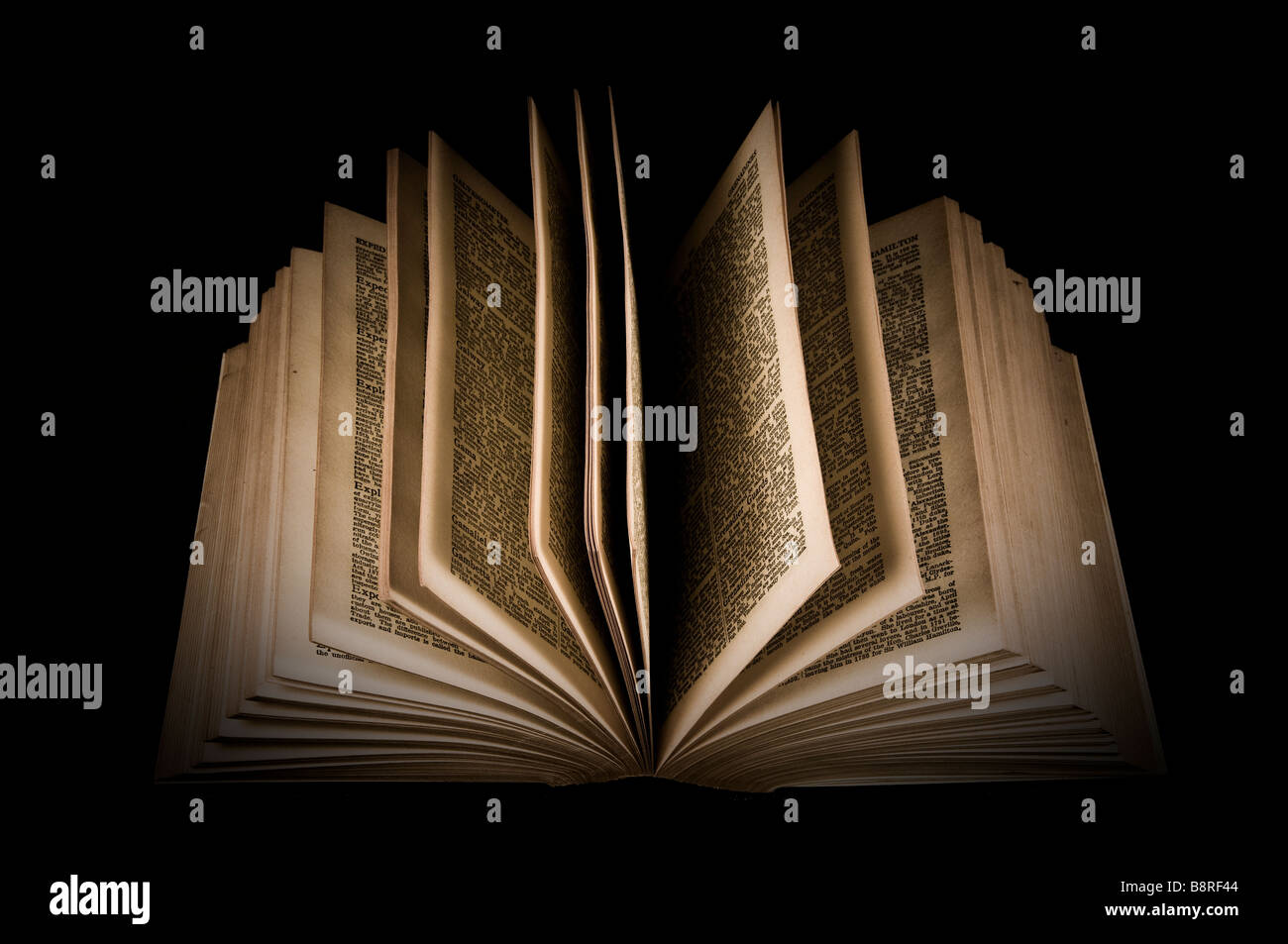 Old encyclopaedia lying open, black background - Stock Image